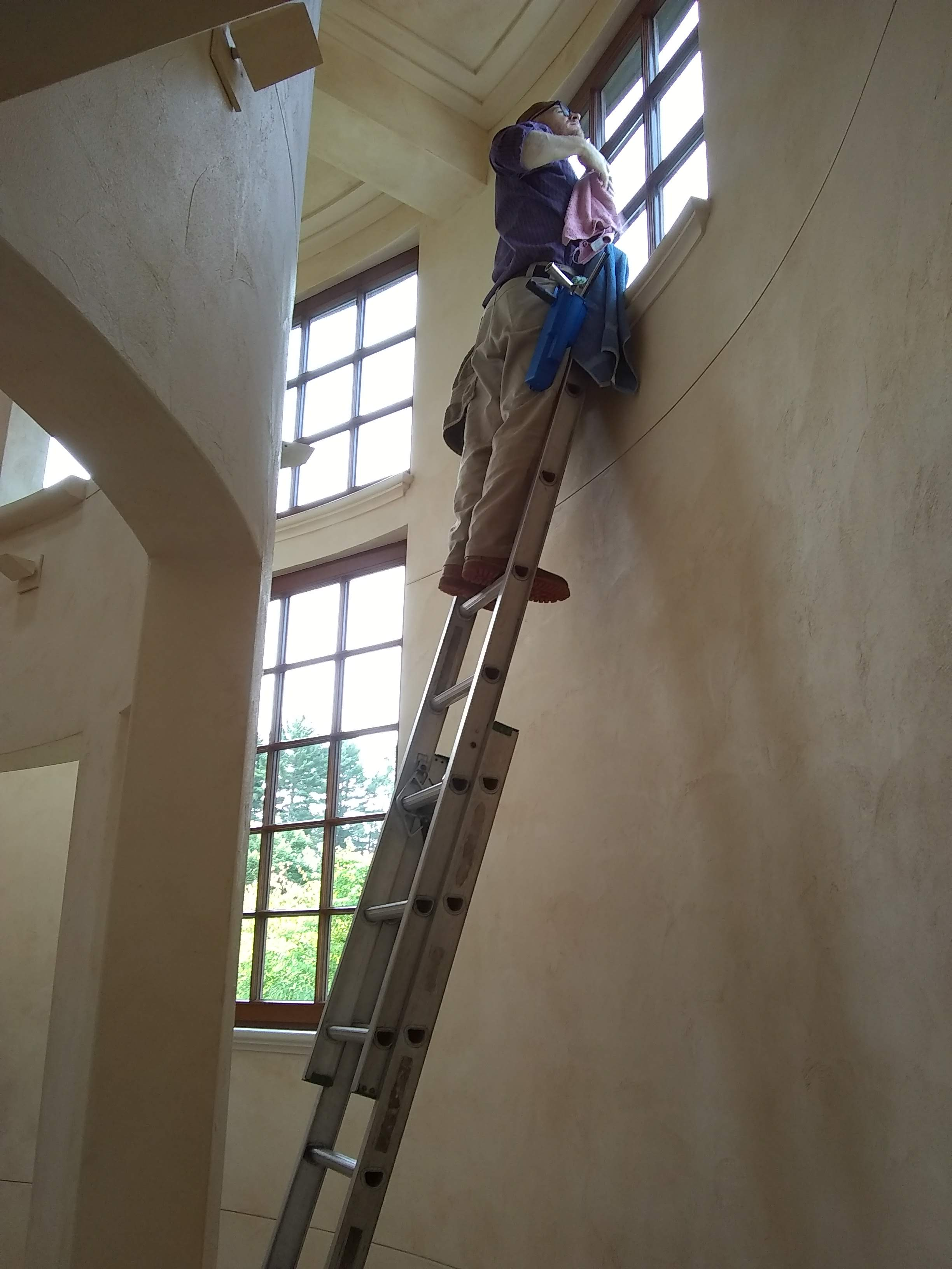 cleaning windows over a staircase
